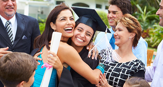 Family around woman graduate student wearing cap with diploma